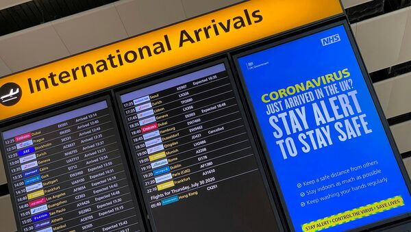 A public health campaign message is displayed on an arrivals information board at Heathrow Airport, following the outbreak of the coronavirus disease (COVID-19), London, Britain, 29 July 2020 - Sputnik International