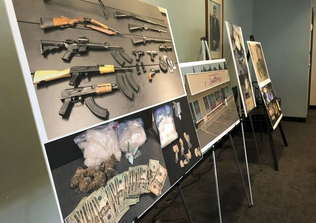 Photos of guns, drugs, and money are displayed at a press conference in Portland, Oregon in 2019