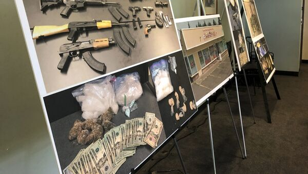 Photos of guns, drugs, and money are displayed at a press conference in Portland, Oregon in 2019 - Sputnik International