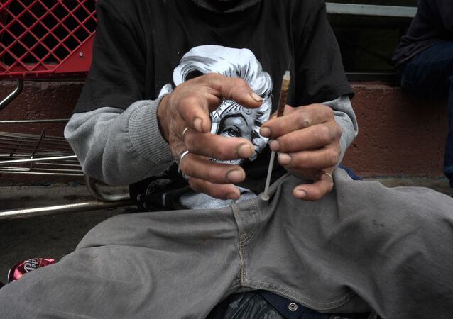 A drug addict prepares a needle to inject himself with heroin in front of a church in the Skid Row area of Los Angeles.