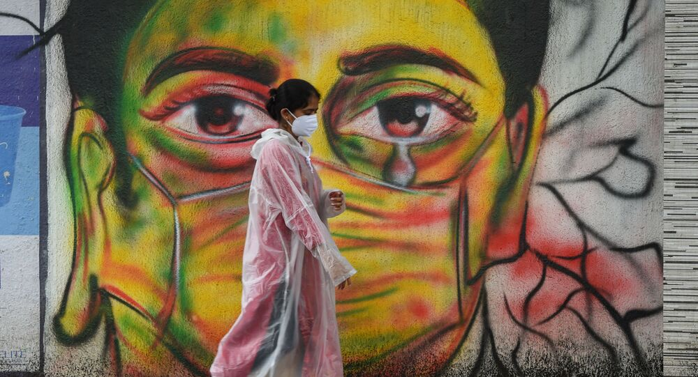 A woman wearing a raincoat walks past a mural depicting a woman with a facemask to spread awareness about the Covid-19 coronavirus, in Mumbai on June 17, 2021