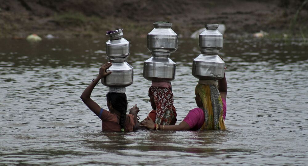Indian women hold each other as they cross the River Heran after collecting drinking water near Sajanpura village in Chhota Udepur district of Gujarat state, India, Tuesday, Aug. 5, 2014