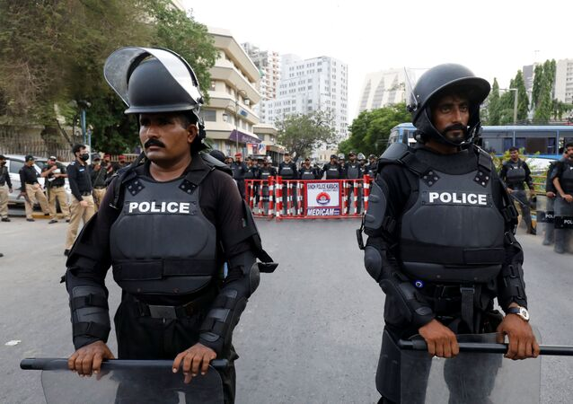 Police officers in riot gear stand guard on a road