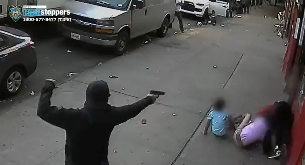 Screenshot from a graphic video showing a gunman shooting a 24-year-old male victim in New York, with two young children narrowly missed