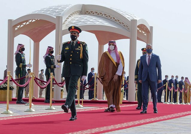 In this March 31, 2021 file photo, released by the Saudi Royal Palace, Saudi Crown Prince Mohammed bin Salman, center right, accompanies Iraqi Prime Minister Mustafa al-Kadhimi on his arrival to Riyadh International Airport, Saudi Arabia. A first round of direct talks held in April 2021, in Iraq, between regional rivals Saudi Arabia and Iran is seen as a positive sign of de-escalation following years of animosity. The hosting of the talks is also a significant step for Iraq, which has ties with both the U.S. and Iran and has often borne the brunt of Saudi-Iran rivalry. (Bandar Aljaloud/Saudi Royal Palace via AP, File)