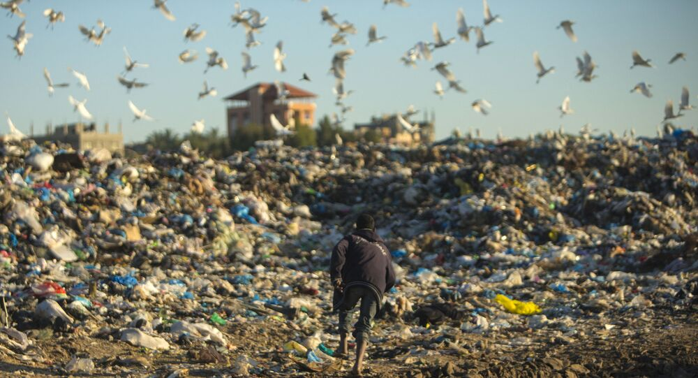 A Palestinian man runs as he collects plastic and other usable items at a garbage dump in Beit Lahia, in the northern Gaza strip, on February 19, 2017. (Photo by MAHMUD HAMS / AFP)
