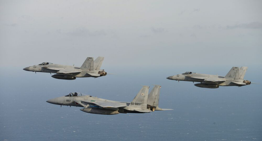 In this Nov. 10, 2017 photo provided by Japan Air Self-Defense Force, two of U.S. F/A-18, left, and right, and Japan Air Self-Defense Force's F-15 fly during a joint military exercise at an undisclosed location.  (Japan Air Self-Defense Force via AP)