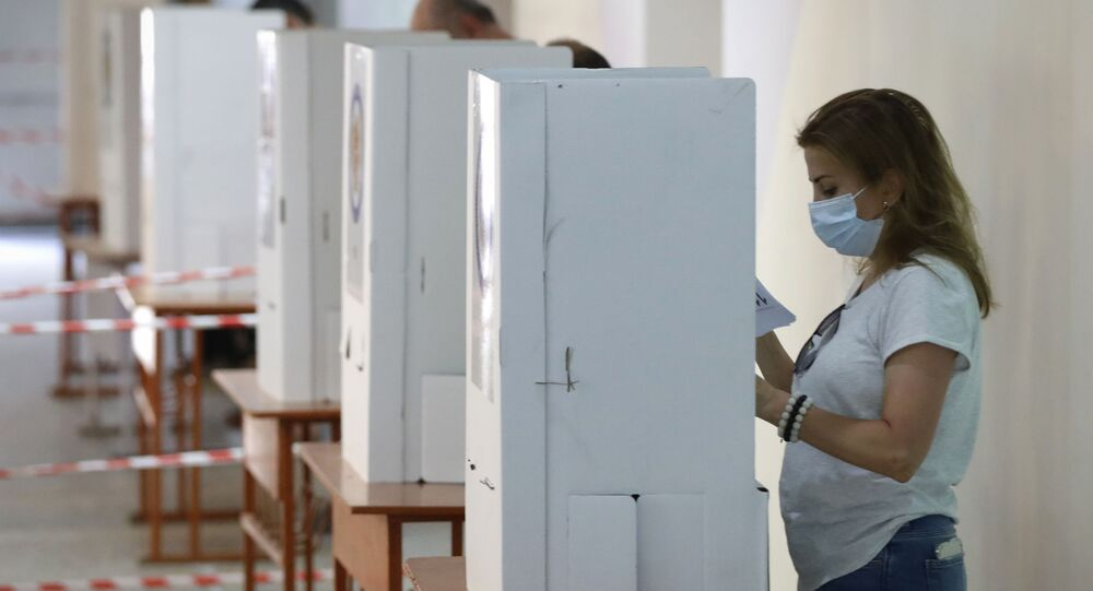 People read their ballot papers at a polling station during a parliamentary election in Yerevan, Armenia, Sunday, 20 June 2021. Armenians are voting in a national election after months of tensions over last year's defeat in fighting against Azerbaijan over the separatist region of Nagorno-Karabakh.