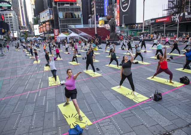People participate in Solstice in Times Square: Mind Over Madness Yoga, an annual all-day outdoor yoga event in New York's Times Square, Sunday, June 20, 2021.