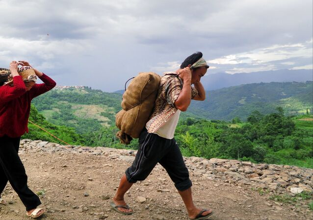 Nagas walk with basket loads of potatoes near Viswema village, in the northeastern Indian state of Nagaland (File)