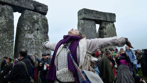 A person looks up as she attends the celebration of the Summer Solstice at Stonehenge ancient stone circle, despite official events being cancelled amid the spread of the coronavirus disease (COVID-19), near Amesbury, Britain, June 21, 2021 - Sputnik International