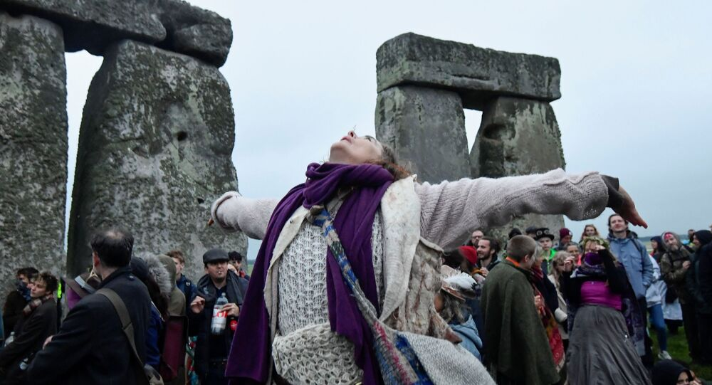A person looks up as she attends the celebration of the Summer Solstice at Stonehenge ancient stone circle, despite official events being cancelled amid the spread of the coronavirus disease (COVID-19), near Amesbury, Britain, June 21, 2021