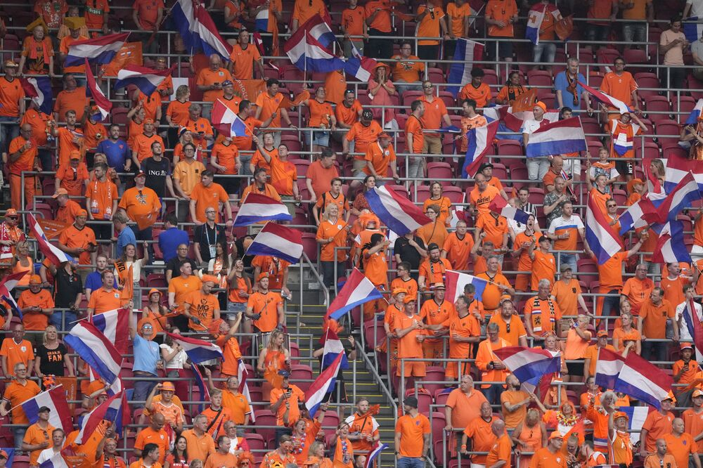 Netherlands fans, who traditionally wear orange, cheer ahead of a Group C football match between the Netherlands and Austria at the Johan Cruyff Arena in Amsterdam.