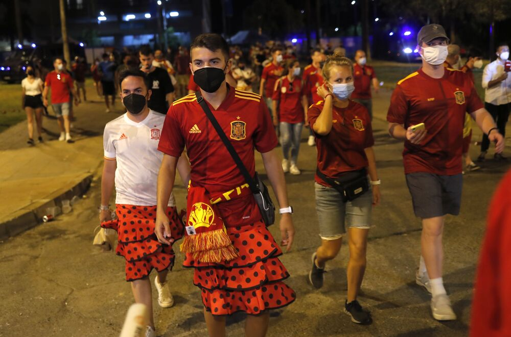 Spain fans wearing skirts traditionally worn by women are seen outside the stadium after a match against Sweden.