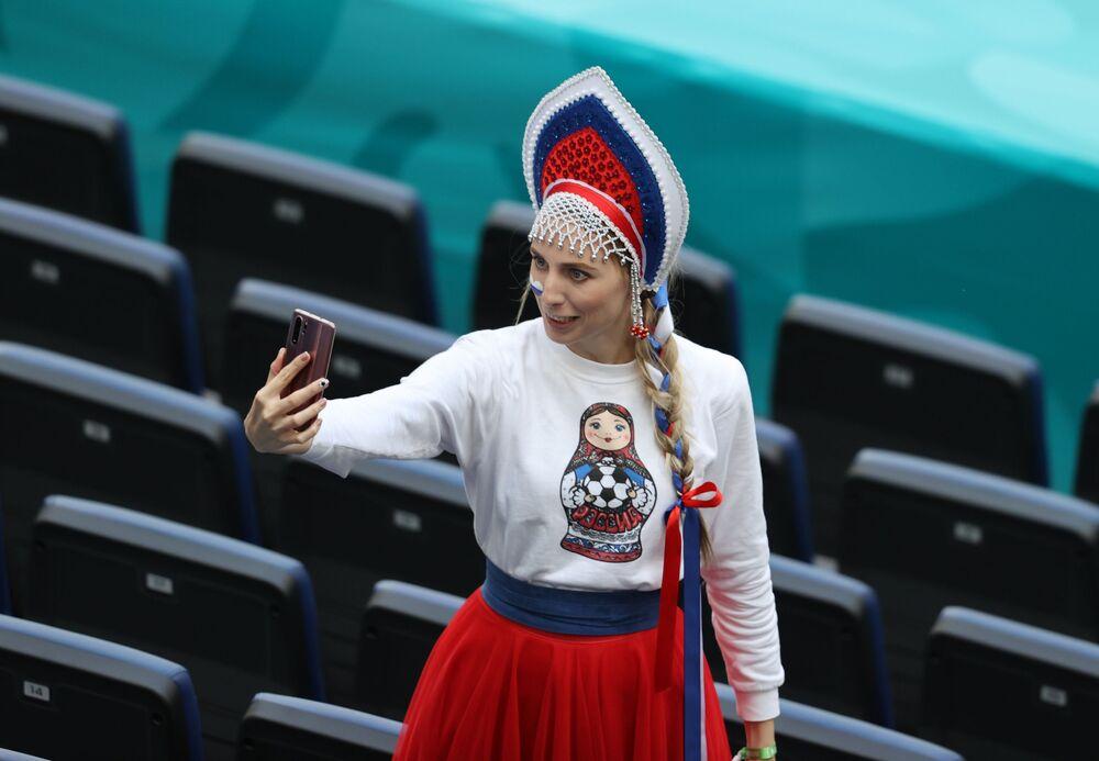 A female Russian fan takes a selfie in a stadium. Many of you have definitely learned the word kokoshnik - a popular decorative headdress.