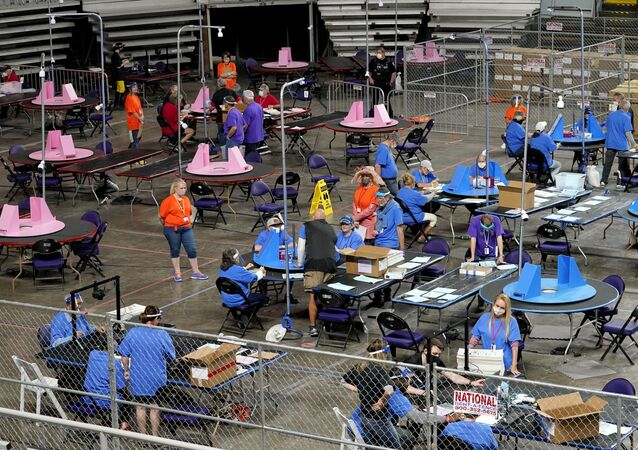 FILE - In this May 6, 2021 file photo, Maricopa County ballots cast in the 2020 general election are examined and recounted by contractors working for Florida-based company, Cyber Ninjas at Veterans Memorial Coliseum in Phoenix. For some conspiracy theorists, the 2020 election still hasn't ended. Trump supporters are pushing to re-examine ballots from November across the country, and finding success in swing states like Arizona and Georgia. Their efforts and sometimes misleading conclusions are being gleefully amplified by the former president.