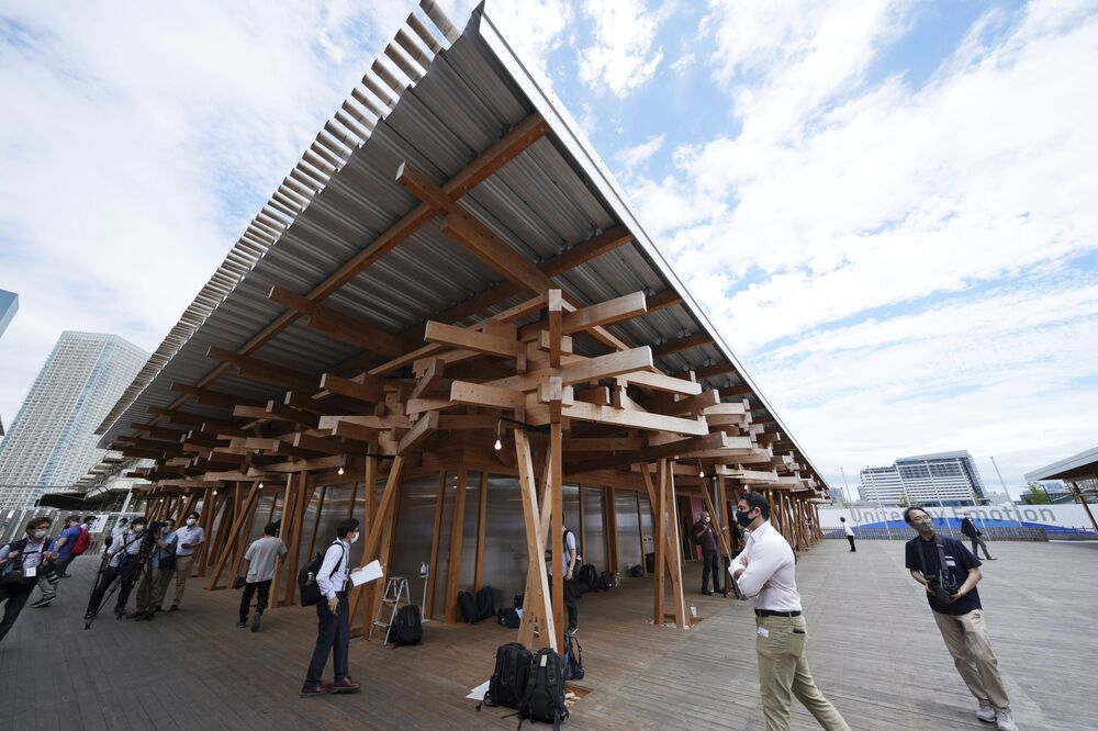 Journalists walk on the Village Plaza near the Tokyo 2020 Olympic and Paralympic Village during a media tour in Tokyo.
