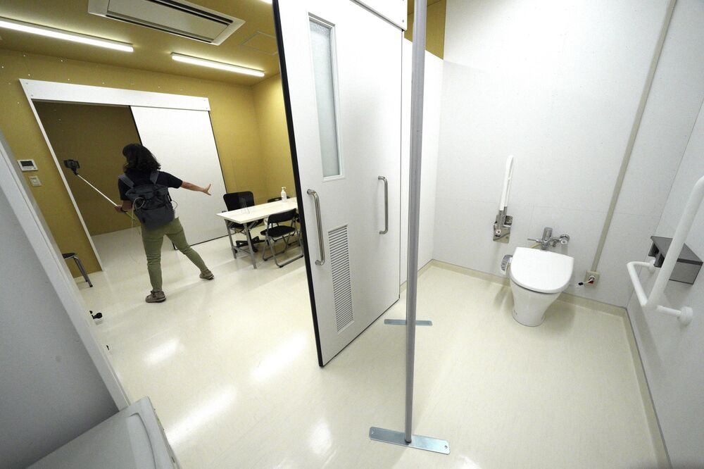 A journalist films a processing room in the Doping Control Station in the Tokyo 2020 Olympic and Paralympic Village during a press tour.