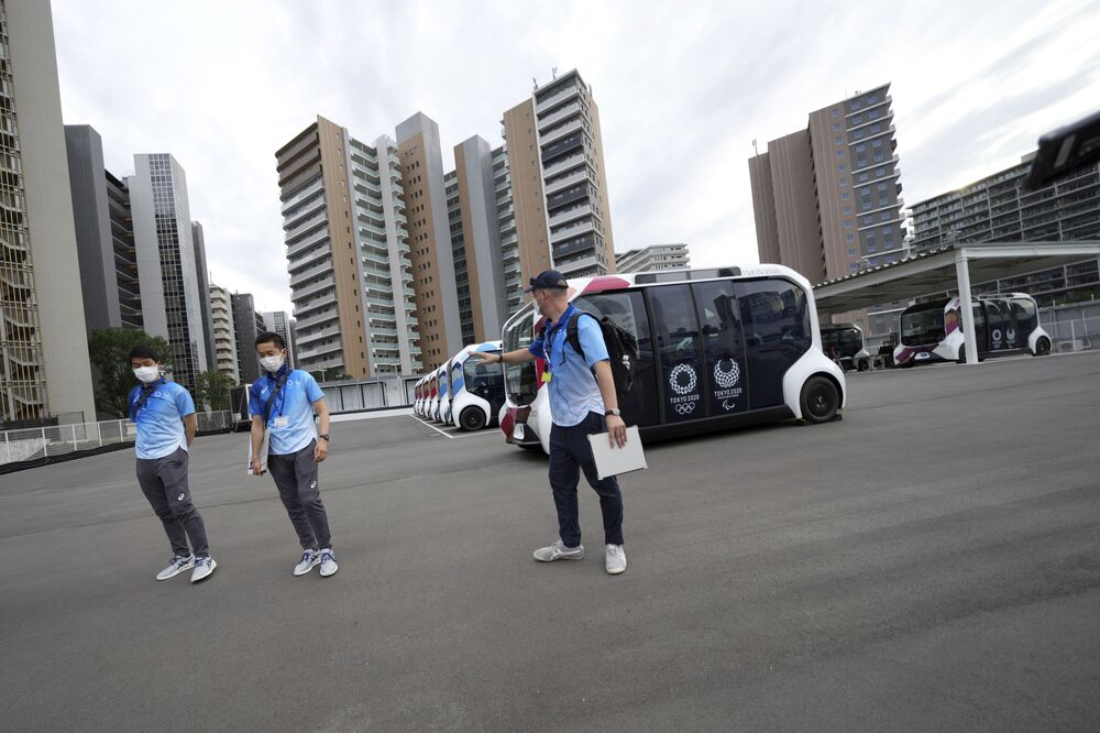 Staff walk near autonomous electric vehicles used around the main facilities during a press tour of the Tokyo 2020 Olympic and Paralympic Village.
