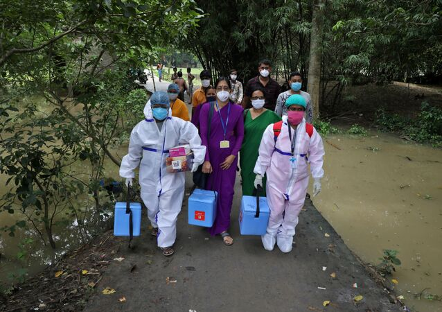 Healthcare workers carry COVISHIELD vaccine, a coronavirus disease (COVID-19) vaccine manufactured by Serum Institute of India, to inoculate villagers during a door-to-door vaccination and testing drive at Uttar Batora Island in Howrah district in West Bengal state, India, June 21, 2021