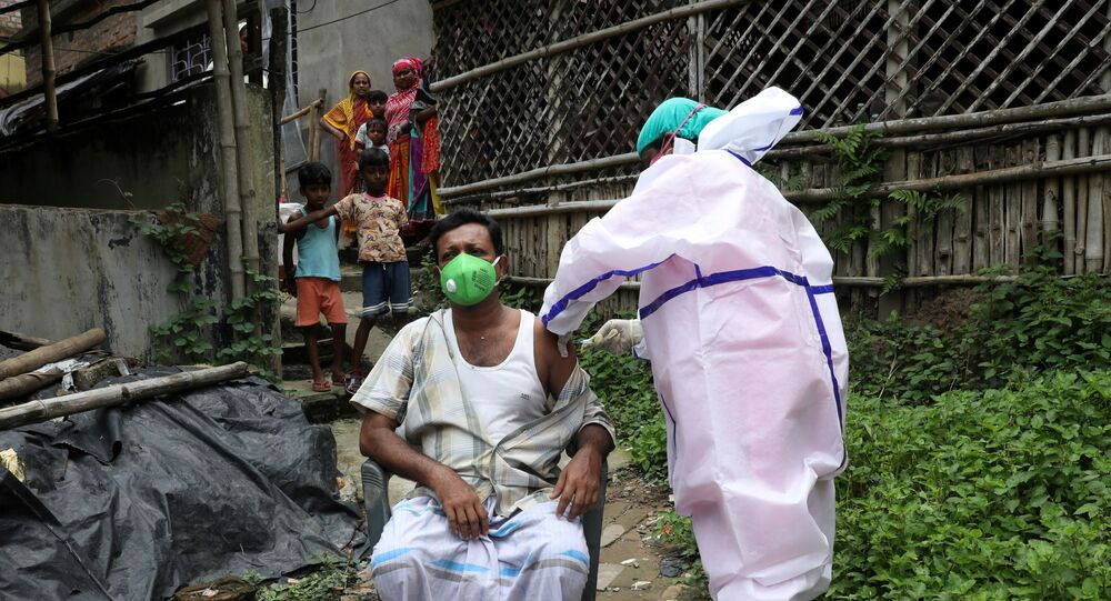 Yusuf Ali, a villager, receives a dose of COVISHIELD vaccine, a coronavirus disease (COVID-19) vaccine manufactured by Serum Institute of India, during a door-to-door vaccination and testing drive at Uttar Batora Island in Howrah district in West Bengal state, India, 21 June 2021