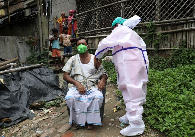 Yusuf Ali, a villager, receives a dose of COVISHIELD vaccine, a coronavirus disease (COVID-19) vaccine manufactured by Serum Institute of India, during a door-to-door vaccination and testing drive at Uttar Batora Island in Howrah district in West Bengal state, India, June 21, 2021