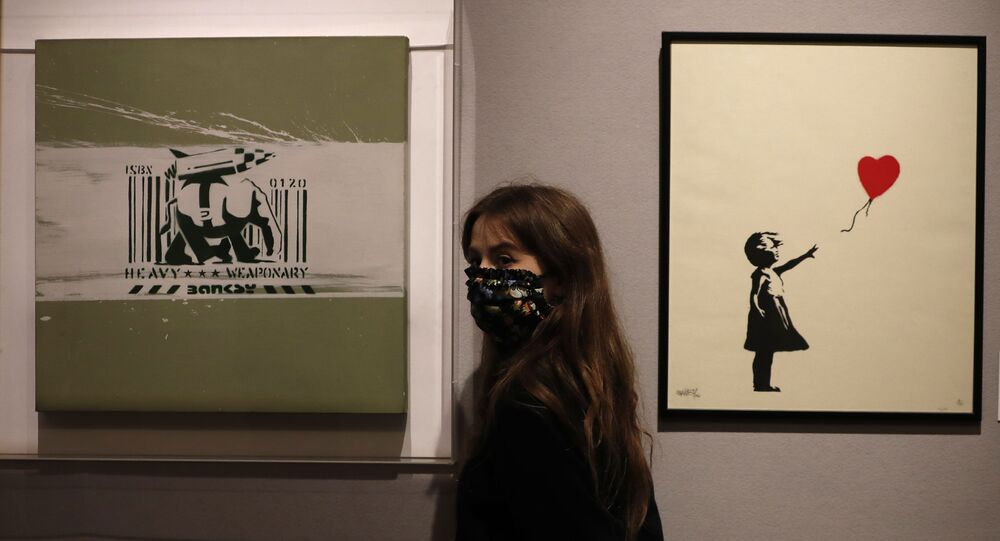 A member of staff from Bonhams auction house stands between two works by British artist Banksy 'Girl with Balloon 2004', right, and 'Heavy Weapon' 2000, in London, Thursday, Oct. 1, 2020