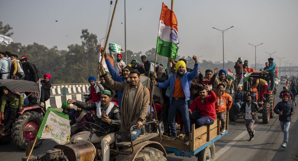 In this 26 January 2021 file photo, protesting farmers ride tractors and shout slogans as they march to the capital breaking down police barricades during India's Republic Day celebrations in New Delhi, India.