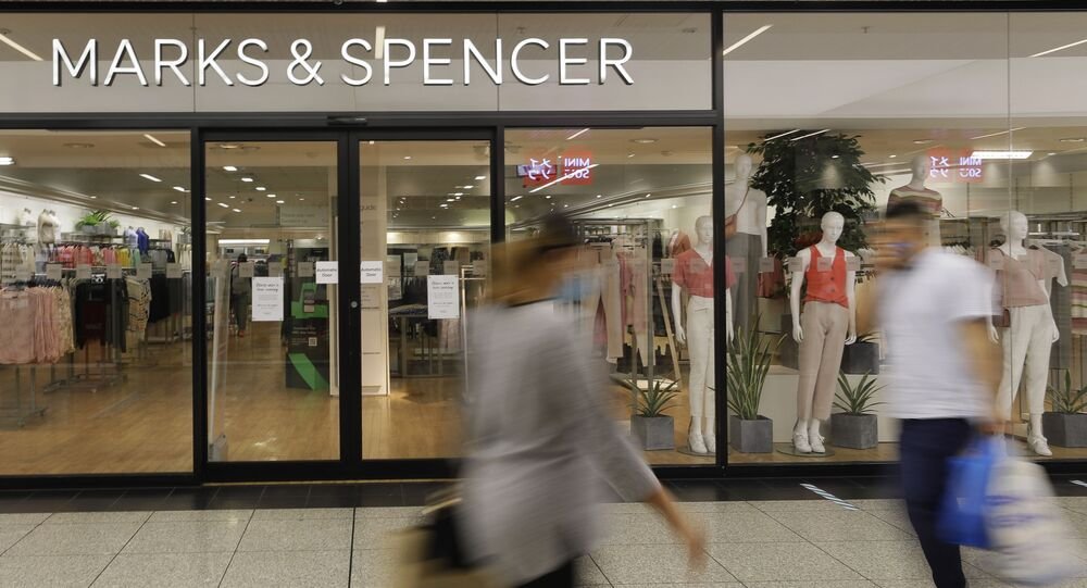 Shoppers pass a branch of Marks and Spencer in London