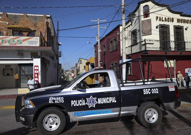 """In this Feb. 10, 2020 file photo, a policeman drives past town hall in Apaseo El Alto, Guanajuato state, Mexico. The notoriously violent Jalisco cartel has responded to Mexico's """"hugs, not bullets"""" policy with a policy of their own: the cartel kidnapped in mid-May 2021, several members of an elite police force in the state of Guanajuato, tortured them to obtain names and addresses of fellow officers, and are now hunting down and killing police at their homes, on their days off, in front of their families."""