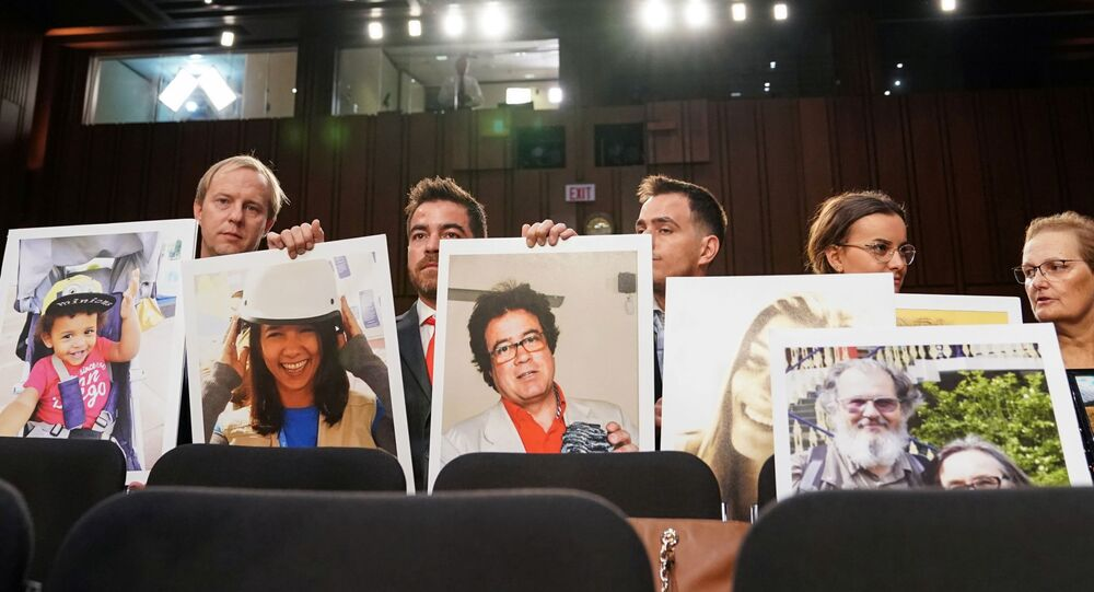 """Family members hold photographs of Boeing 737 MAX crash victims lost in two deadly 737 MAX crashes that killed 346 people as Boeing CEO Dennis Muilenburg testifies before a Senate Commerce, Science and Transportation Committee hearing on """"aviation safety"""" and the grounded 737 MAX on Capitol Hill in Washington, U.S., October 29, 2019"""