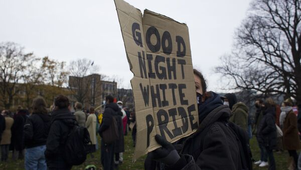 A woman holds a placard during an anti-racism rally organized by KOZP, Kick Out Zwarte Piet, or Kick Out Black Pete, in The Hague, Netherlands, Sunday, Dec. 6, 2020.  - Sputnik International