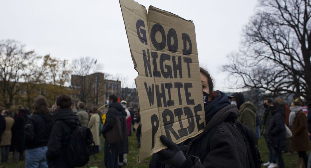 A woman holds a placard during an anti-racism rally organized by KOZP, Kick Out Zwarte Piet, or Kick Out Black Pete, in The Hague, Netherlands, Sunday, Dec. 6, 2020.