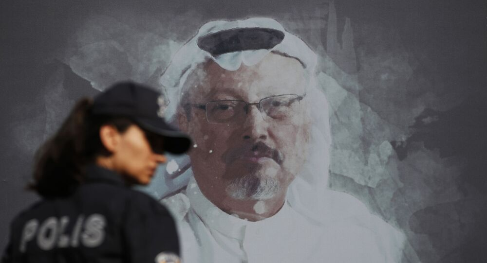 In this Wednesday, Oct. 2, 2019 file photo, a Turkish police officer walks past a picture of slain Saudi journalist Jamal Khashoggi prior to a ceremony, near the Saudi Arabia consulate in Istanbul, marking the one-year anniversary of his death.
