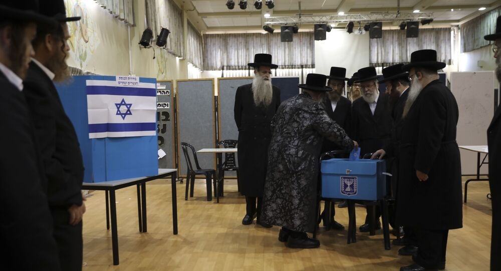 FILE - In this Tuesday, Sept. 17, 2019 file photo, ultra-Orthodox Jews watch Rabbi Israel Hager vote in Bnei Brak, Israel. Prime Minister Benjamin Netanyahu has called on his rival, Benny Gantz, to join a unity government, after unprecedented repeat elections returned a near tie between the two main parties.