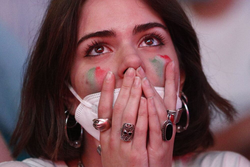 An Italian fan is on the edge of her seat as she watches the match at Rome's Stadio Olimpico between Turkey and Italy on a big screen in Rome on 11 June 2021. Italy won the match 3-0.