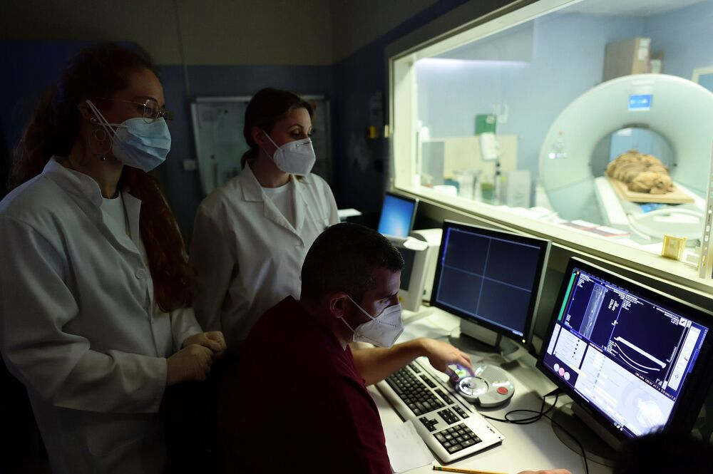 Medical radiology technicians and researchers look at a computer screen as an Egyptian mummy undergoes a CT scan.