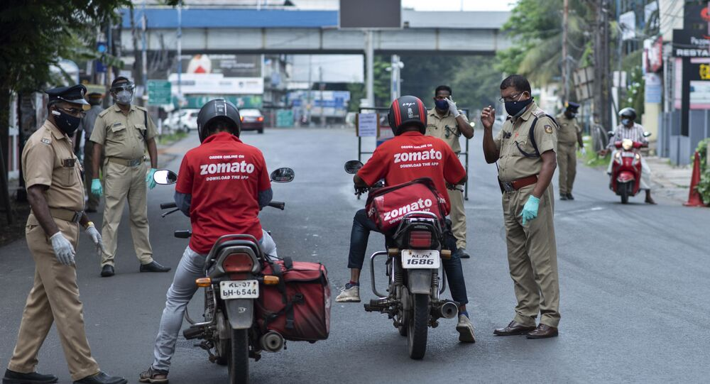 Policemen check the credentials of food delivery personnel during a lockdown imposed to curb the spread of coronavirus in Kochi, Kerala state, India, Saturday, May 8, 2021