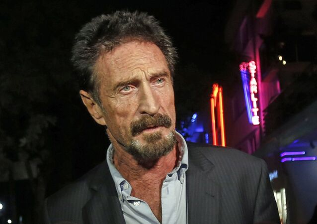 FILE — In this Dec. 12, 2012 file photo, anti-virus software founder John McAfee answers questions to reporters as he walks on Ocean Drive, in the South Beach area of Miami Beach, Fla.