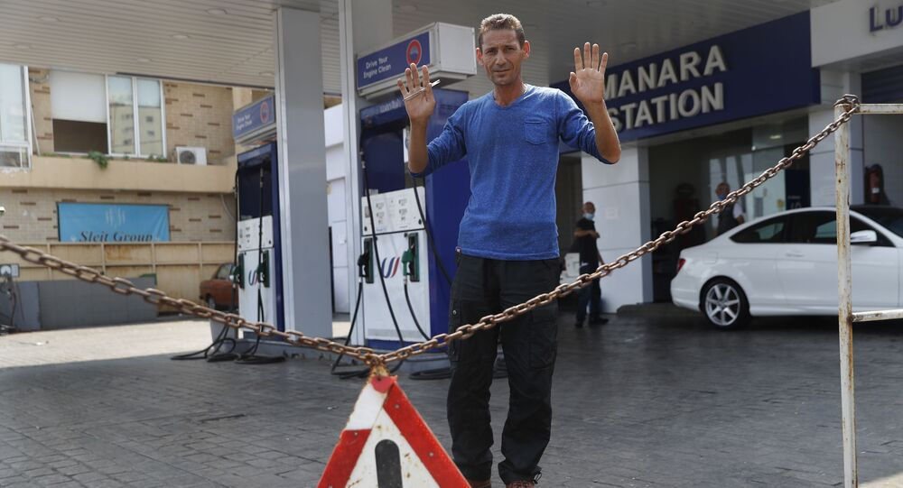 A gas station workers gestures as he saying no fuel at the station, in Beirut, Lebanon, Wednesday, July 29, 2020.