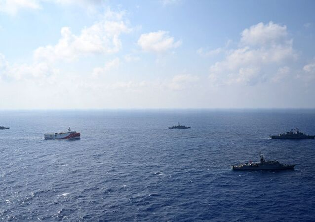 In this photo provided by the Turkish Defense Ministry, Turkey's research vessel, Oruc Reis, in red and white, is surrounded by Turkish navy vessels as it was heading in the west of Antalya on the Mediterranean, Turkey, Monday, Aug 10, 2020.