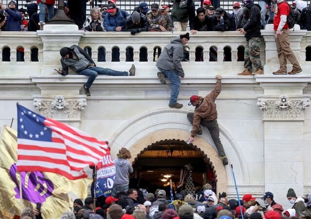 A mob of supporters of U.S. President Donald Trump fight with members of law enforcement at a door they broke open as they storm the U.S. Capitol Building in Washington, U.S., January 6, 2021.