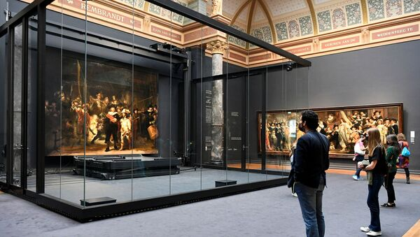 Poeple look at Rembrandt's famed Night Watch, which is back on display in what researchers say in its original size, with missing parts temporarily restored in an exhibition aided by artificial intelligence, at Rijksmuseum in Amsterdam, Netherlands June 23, 2021.  - Sputnik International