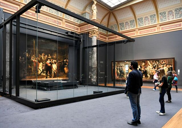 Poeple look at Rembrandt's famed Night Watch, which is back on display in what researchers say in its original size, with missing parts temporarily restored in an exhibition aided by artificial intelligence, at Rijksmuseum in Amsterdam, Netherlands June 23, 2021.