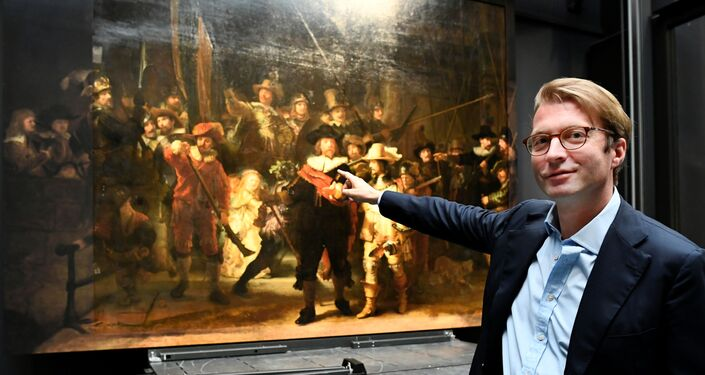 Museum director Taco Dibbits points to Rembrandt's famed Night Watch, which is back on display in what researchers say in its original size, with missing parts temporarily restored in an exhibition aided by artificial intelligence, at Rijksmuseum in Amsterdam, Netherlands June 23, 2021.