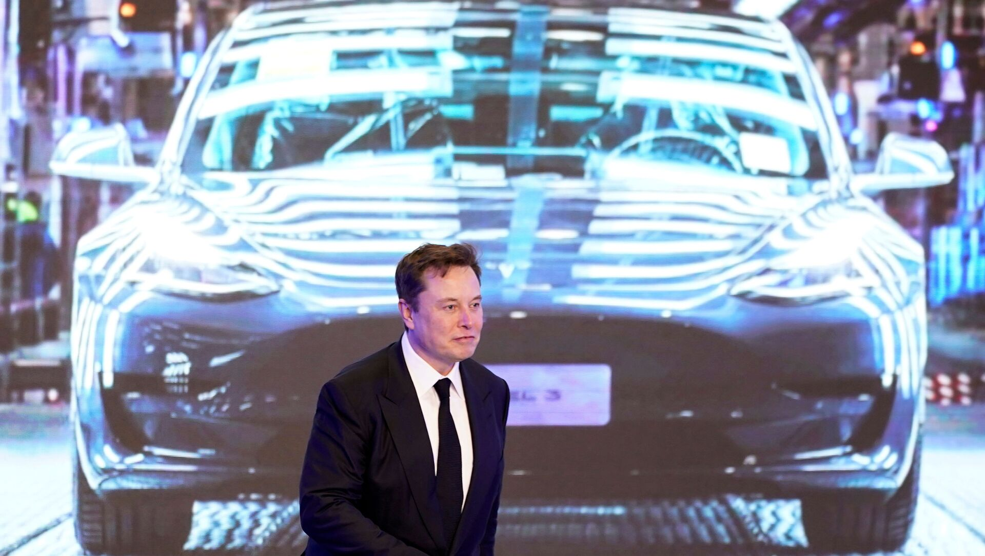 Tesla Inc CEO Elon Musk walks next to a screen showing an image of Tesla Model 3 car during an opening ceremony for Tesla China-made Model Y program in Shanghai, China January 7, 2020. - Sputnik International, 1920, 27.07.2021