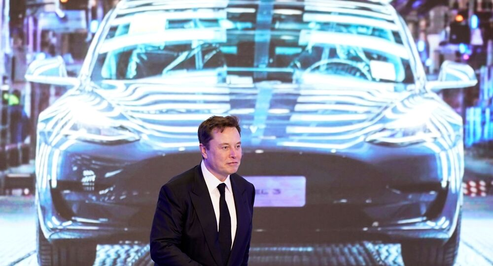Tesla Inc CEO Elon Musk walks next to a screen showing an image of Tesla Model 3 car during an opening ceremony for Tesla China-made Model Y program in Shanghai, China January 7, 2020.