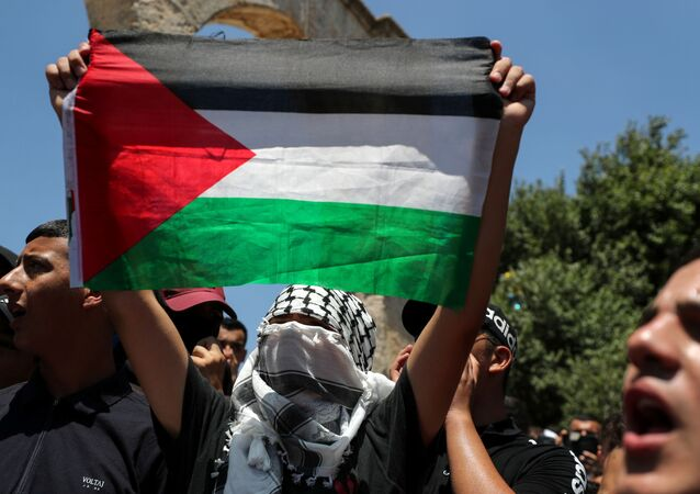 A demonstrator holds a Palestinian flag during a protest over the death of Nizar Banat, at the compound that houses Al-Aqsa Mosque, known to Muslims as Noble Sanctuary and to Jews as Temple Mount, in Jerusalem's Old City, June 25, 2021.