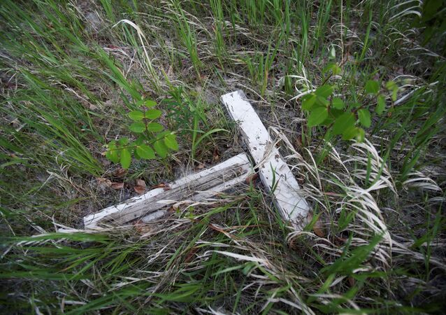 A decaying white cross lies in a small cemetery for children who died at Brandon Indian Residential School near one of three sites where researchers, partnered with the Sioux Valley Dakota Nation, located 104 potential graves in Brandon, Manitoba, Canada June 12, 2021.