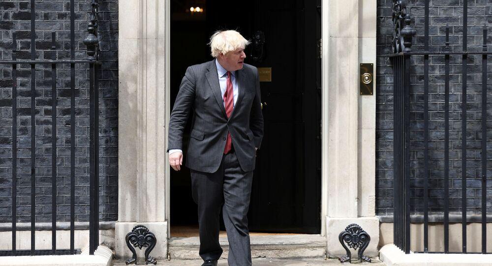 Britain's Prime Minister Boris Johnson walks at Downing Street in London